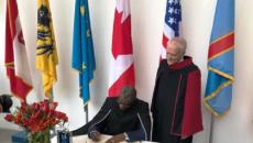 Dr Denis Mukwege couchant les écrits dans le livre d'or de l'université d'Anvers