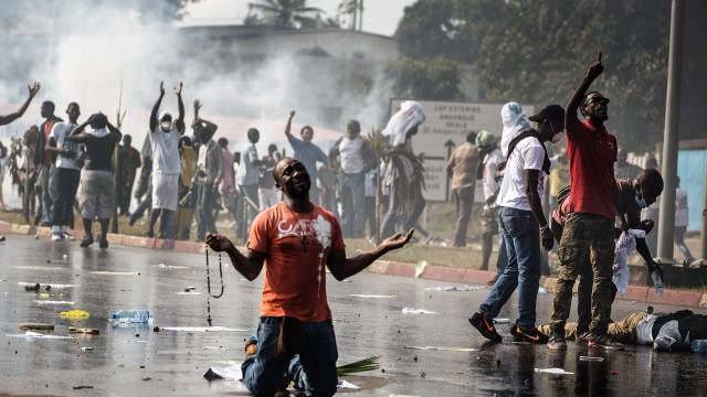 A supporter of Gabonese opposition leader Jean Ping prays in front of security forces blocking a demonstration trying to reach the electoral commission in Libreville on August 31, 2016 as another protestor lays on the ground in distress. Bongo won by a narrow 5,594 votes of a total 627,805 registered voters. Turnout was 59.46 percent nationwide but soared to 99.93 percent in one of the country's nine provinces -- the Haut-Ogooue, heartland of Bongo's Teke ethnic group -- in a result hotly contested by the opposition. / AFP / MARCO LONGARI        (Photo credit should read MARCO LONGARI/AFP/Getty Images)