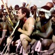 (FILES) A file photo taken on March 27, 1989 in Keate's Drift shows Johnny Clegg (C), leader of the pop group Savuka, in a traditional Zulu outfit during his wedding with Jennifer Bartlett. South African legendary singer Johnny Clegg, who blended Zulu rhythms with Western styles, died on July 16, 2019, after a long battle with cancer, his manager said. Clegg succumbed to pancreatic cancer at the age of 66 at his home in Johannesburg, more than four years after he was diagnosed. / AFP / Trevor SAMSON